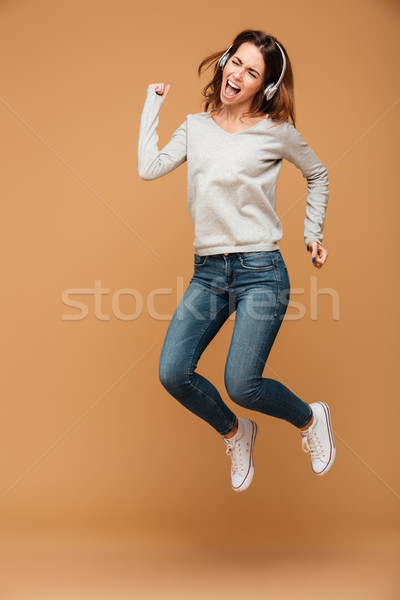 Full length photo of young attractive woman in headphones jumpin Stock photo © deandrobot
