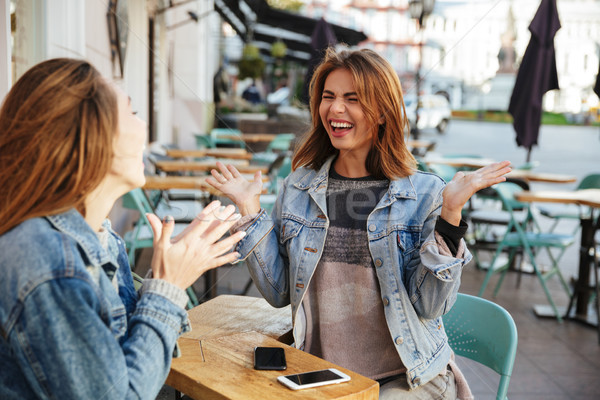 Two emotional young girls talking while sitting in city cafe Stock photo © deandrobot
