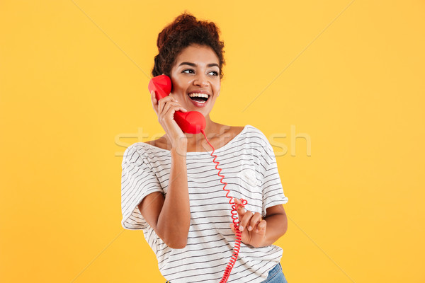 Cheerful lady talking on red telephone and looking aside Stock photo © deandrobot