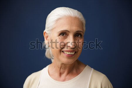 Photo of charming mature woman in beige tshirt, holding her chin Stock photo © deandrobot