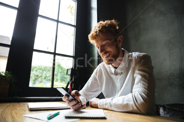 Portrait of a smiling redhead man using mobile phone Stock photo © deandrobot