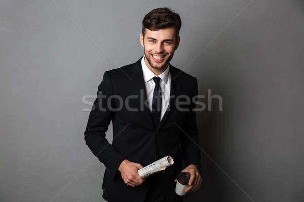 Young smiling bearded man in formalwear holding newspaper and cu Stock photo © deandrobot