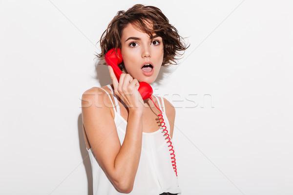 Geschokt jonge vrouw praten Rood retro telefoon Stockfoto © deandrobot