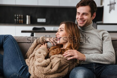 Loving coupe sitting on sofa at home watch TV Stock photo © deandrobot