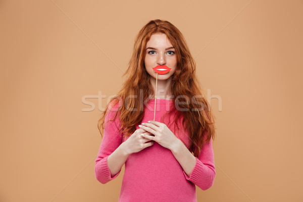 Portrait of a happy young redhead girl holding paper lips Stock photo © deandrobot