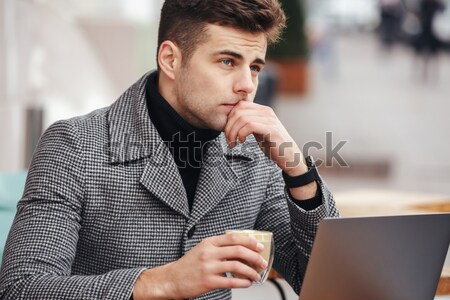 Photo of businesslike man working with silver laptop in cafe out Stock photo © deandrobot