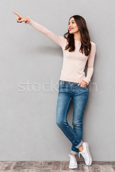 Full-length image of positive adult girl with brown hair pointin Stock photo © deandrobot