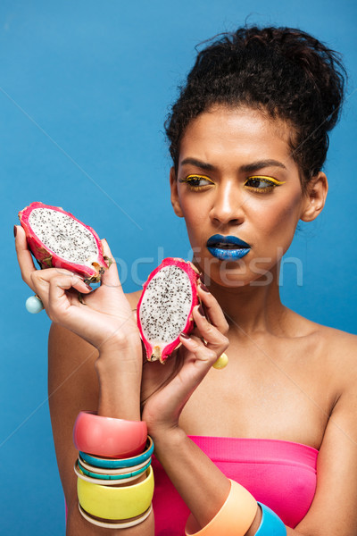 Photo of fascinating afro woman with colorful cosmetics on face  Stock photo © deandrobot