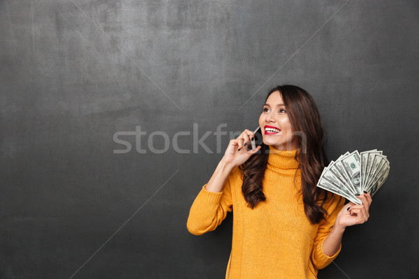 Smiling woman in sweater holding money and talking by smartphone Stock photo © deandrobot