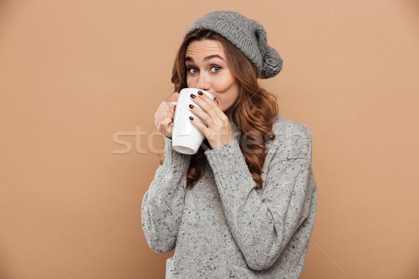 Güzel kız gri şapka örgü kazak içme Stok fotoğraf © deandrobot