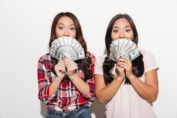 Two asian pretty cute ladies covering faces with money. Stock photo © deandrobot
