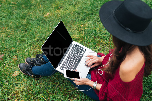 Top view of a young woman in hat using laptop Stock photo © deandrobot