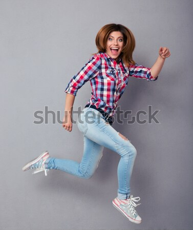 Full length image of cheerful ginger woman in shirt Stock photo © deandrobot