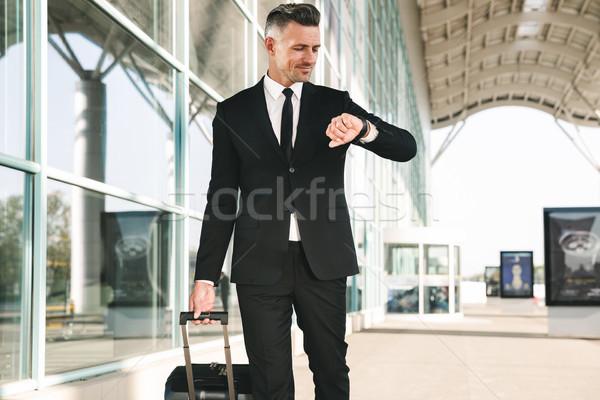 Smiling businessman dressed in suit walking Stock photo © deandrobot