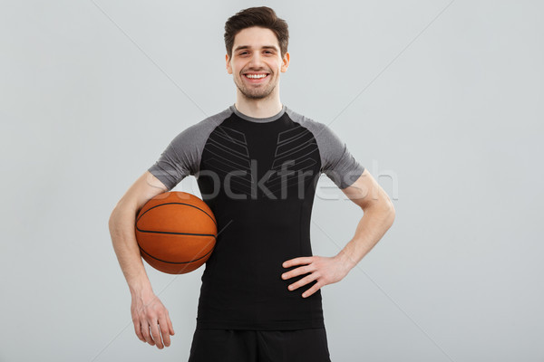 Portrait of a satisfied young sportsman with a basketball Stock photo © deandrobot