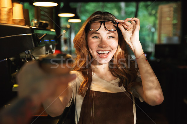 Portrait of a smiling young barista girl in apron Stock photo © deandrobot
