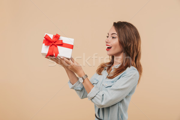 Portrait of an excited young girl looking at present box Stock photo © deandrobot