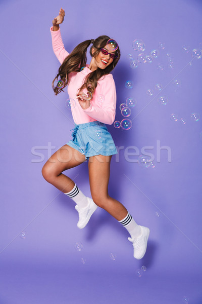 Full length portrait of stylish teenage girl with two ponytails  Stock photo © deandrobot