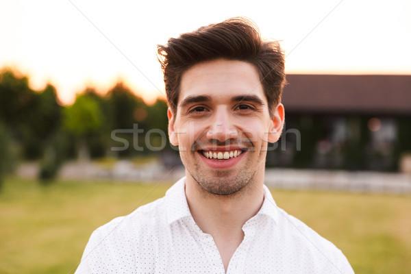 Photo closeup of cheerful young man wearing white shirt smiling, Stock photo © deandrobot
