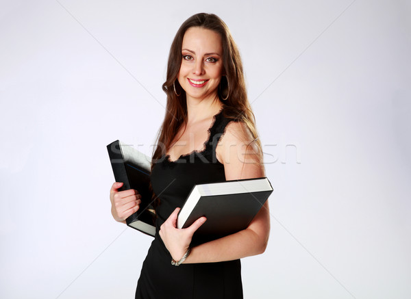 Smiling woman standing and holding books over gray background Stock photo © deandrobot