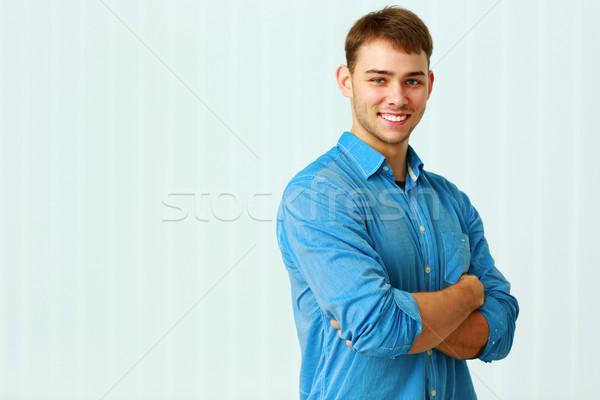 Jóvenes feliz empresario pie armas doblado Foto stock © deandrobot