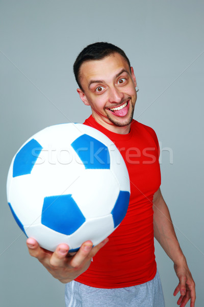 Funny sportive man holding soccer ball on gray background Stock photo © deandrobot