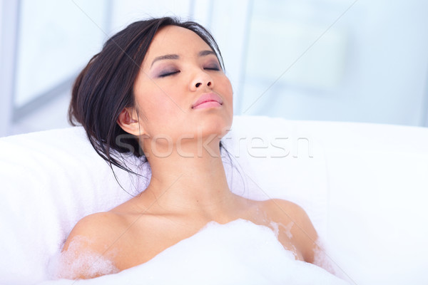 Relaxed asian woman resting in her bathtub Stock photo © deandrobot