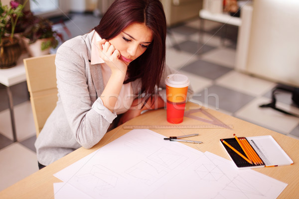 Pensive young architect having a problem with her technical drawings Stock photo © deandrobot