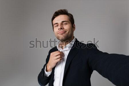 Confident businessman straightening his tie Stock photo © deandrobot