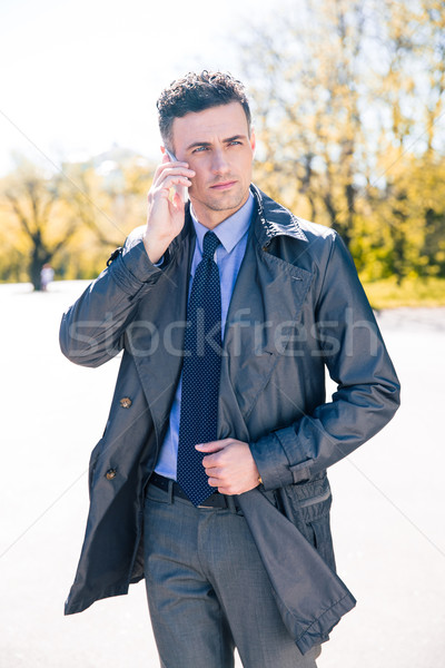 Handsome businessman talking on the phone outdoors Stock photo © deandrobot