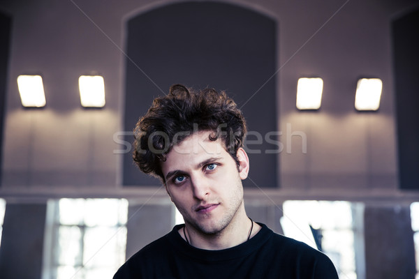 Portrait of a young serious man with curly hair Stock photo © deandrobot