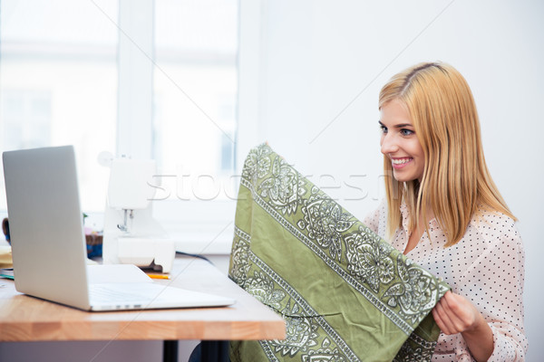 Female tailor holding cloth and looking on laptop screen Stock photo © deandrobot