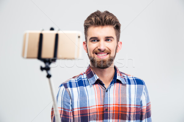 Portrait of a cheerful young man making selfie photo Stock photo © deandrobot