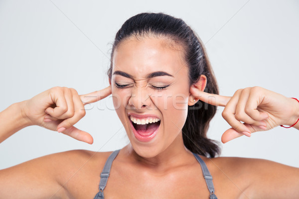 Woman covering her ears with fingers and shouting Stock photo © deandrobot