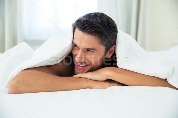 Man lying under blanket on the bed at home Stock photo © deandrobot