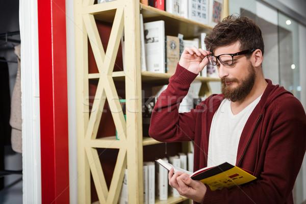 Brodaty młody człowiek czytania książki stałego półka na książki Zdjęcia stock © deandrobot