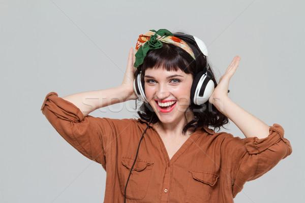 Heureux jeune femme casque écouter de la musique isolé Photo stock © deandrobot