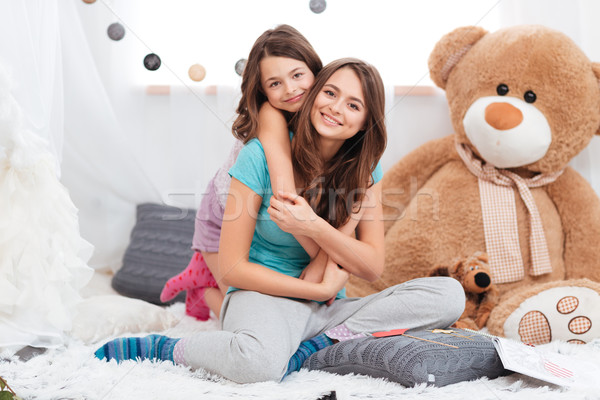 Two cheerful charming sisters sitting in children room  Stock photo © deandrobot