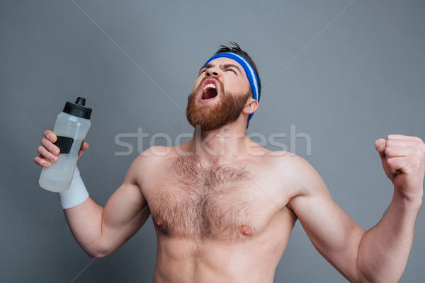 Furious bearded sportsman with bottle of water standing and shouting Stock photo © deandrobot