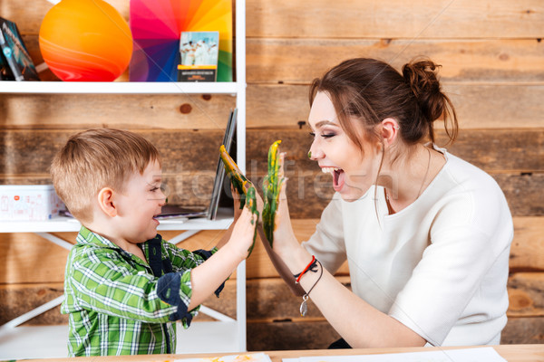 Mother and little son giving high five with painted hands  Stock photo © deandrobot