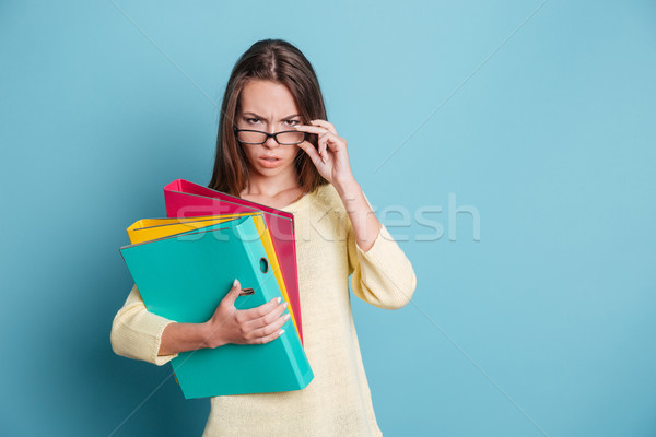 Seriously looking smart girl with colorful binders Stock photo © deandrobot