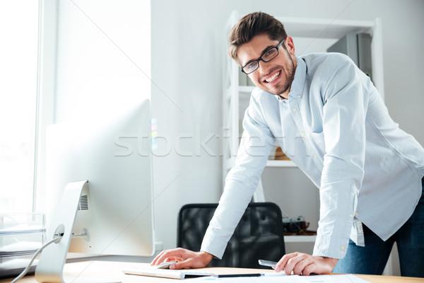 Derűs fiatal üzletember áll számítógéphasználat iroda Stock fotó © deandrobot
