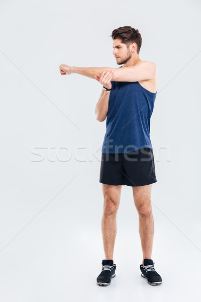 Handsome young sportsman stretching hands during workout Stock photo © deandrobot