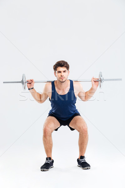 Muscular fitness man doing heavy exercise using barbell Stock photo © deandrobot
