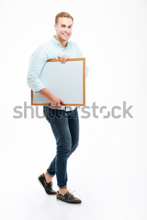 Full length of cheerful young man walking and holding whiteboard Stock photo © deandrobot