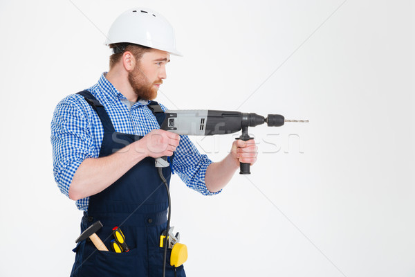 Profile of concentrated handsome young builder using modern drill Stock photo © deandrobot