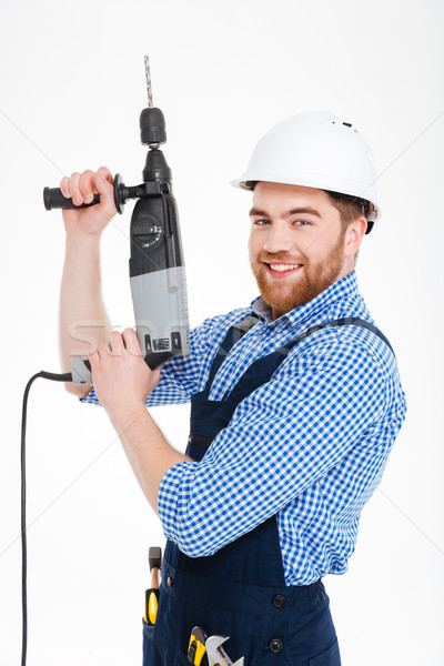 Happy attractive young worker standing and smiling using drill Stock photo © deandrobot