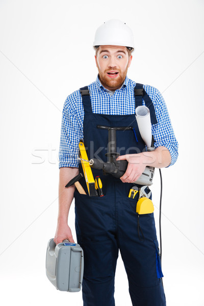 Amazed builder in helmet holding tool box, drill and blueprints Stock photo © deandrobot