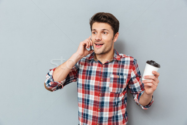 Hnadsome man talking on cell phone and drinking takeaway coffee Stock photo © deandrobot