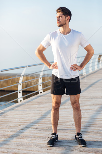 Sportsman standing on wooden terrace in the morning Stock photo © deandrobot